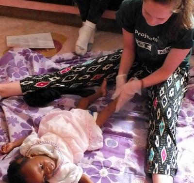 An Occupational Therapy intern helps a young girl move her legs in Kenya