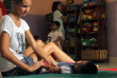A Projects Abroad Physical Therapy intern treats a Cambodian child with special needs at the National Borei for Infants and Children in Cambodia