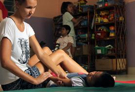 A Physical Therapy intern in Cambodia assists a child during her volunteer project.