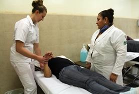 A student on the Physical Therapy Internship in Mexico learns new stretches from her supervisor.