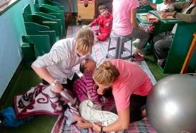 Physical therapy interns help a young child during treatment in Nepal.