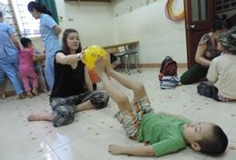 A Physical Therapy intern in Vietnam plays a game with a boy during a session.