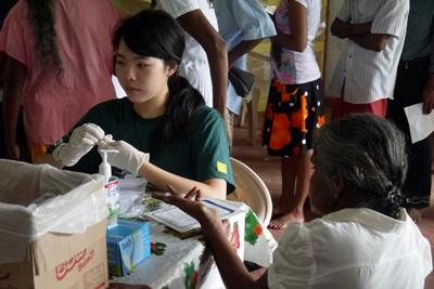 A Projects Abroad intern checks a Sri Lankan woman's blood sugar levels in Colombo.