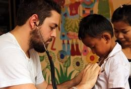 A public health intern examines a young boy in Cambodia.