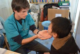 A volunteer on the Morocco Speech Therapy Internship assists a young boy.