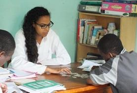 An intern on the Togo Speech Therapy Project helps a young child identify words.