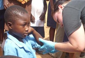 A nursing volunteer abroad checks a young boy's wound.
