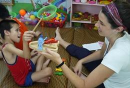 An intern on the Occupational Therapy Project abroad assists a young child in a developing country.
