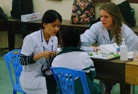 A pharmacy intern observes a pharmacist as she assists a patient.