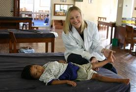 A student on the Physical Therapy Internship focuses on a child's leg during assessment.