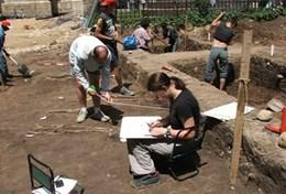 Professional archaeologists work abroad and take notes at a local digging site in Romania.