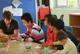 Vietnamese children with autism receive an activity from a professional volunteer psychologist.