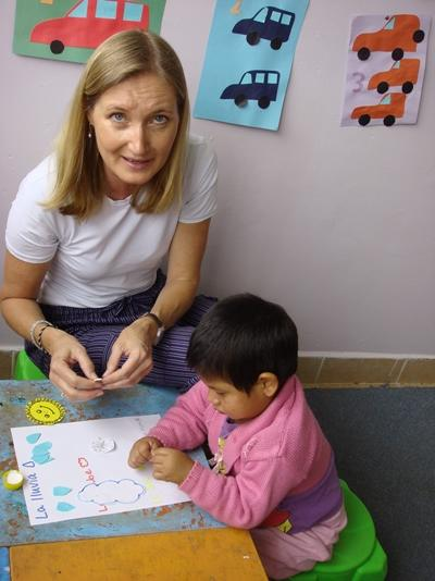 A Bolivian child completes an activity with the help of a Projects Abroad volunteer.
