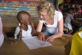 A volunteer social worker assists a young child in Ghana with his activity as part of a professional assessment.