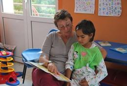 A social worker volunteering in Romania works with a young child in the classroom.