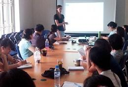 A professional social worker gives a presentation to local staff in a Vietnam placement.