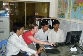 A professional journalist in Cambodia explains her story to staff in the office.