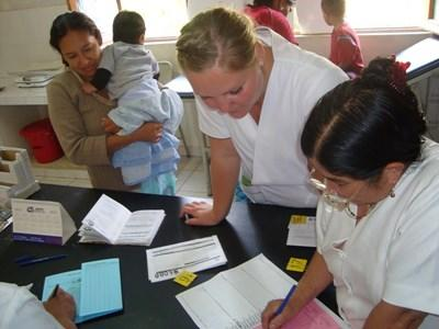 Professional volunteer working with local staff on site nutrition project in Bolivia