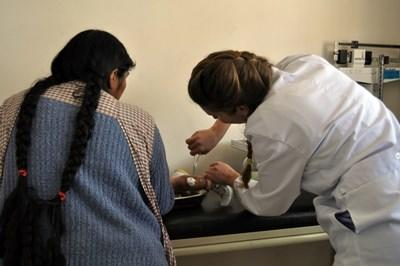 Professional volunteer working with patient and mother on volunteer project in Bolivia