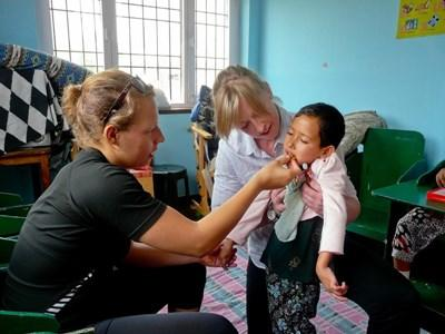 Professional doctors working on volunteer project with child in Nepal