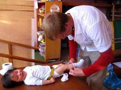 Professional volunteer working with child on medicine project in Peru