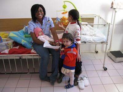 Professional massage therapist volunteering with children in Romania