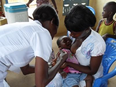 Professional nurse on the Nursing project in Ghana treats a mother and her child