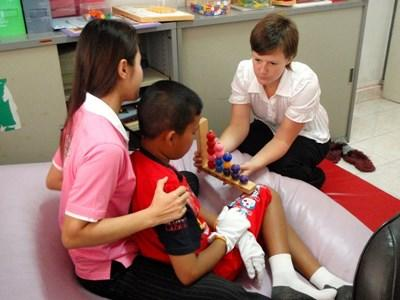 Physical therapist gives child a counting activity in a clinic in Cambodia