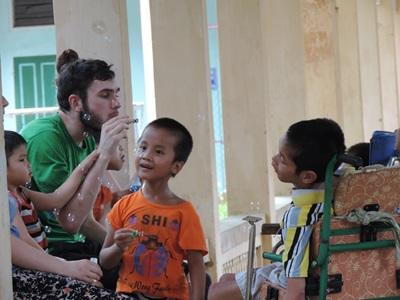 A volunteer works with disabled children at a Speech Therapy project in Vietnam