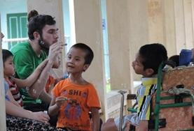 A speech therapist volunteering with children at a rehabilitation center in Vietnam.