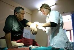 A professional acupuncturist assists a man in a hospital based in Nepal.