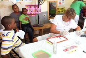 A professional dentistry volunteer assists young children in Jamaica on the Professional Denal Project.