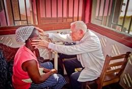 A volunteer doctor examines a local woman in Ghana as part of his project abroad.