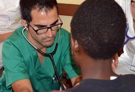 Based in Jamaica, a volunteer doctor takes a photo with his patients at his placement.