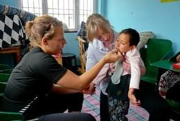 Professional volunteer doctors examine a young child on their project in Nepal.