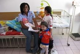 A qualified massage therapist works with young children at a care centre in Romania.