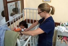 A professional volunteer occupational therapist works works with a young girl in Bolivia.
