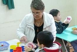 Based in Vietnam, a professional occupational therapist assists a young child during a therapy session.