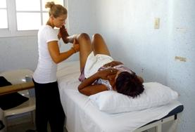 A physical therapist volunteering in Jamaica, with one of her patients.