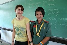 A professional teacher volunteering in Thailand with one of her students in a classroom.
