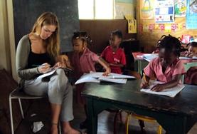 A professional teacher volunteering in Jamaica marks a child's work.