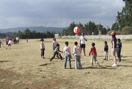 A professional PE teacher volunteering in Ethiopia encourages children to get active during a class.