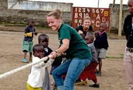 A special needs teacher volunteering in Ghana spends time outdoors with local children.