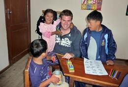 A special needs teacher volunteering in Bolivia helps children with an educational activity.