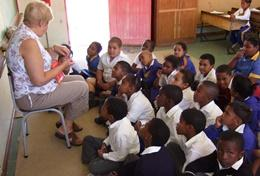 A qualified professional teacher volunteering in South Africa teaches a class at a local school.