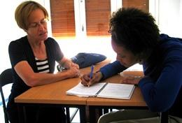 A professional teacher volunteering abroad helps a local student with an exercise at a school.