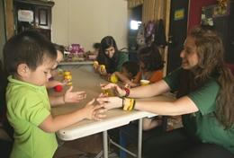A volunteer works with a child during an arts and crafts activity in class.