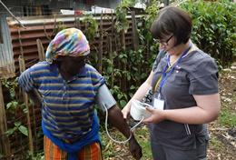 A professional doctor volunteering abroad checks blood pressure at an outreach