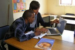 A volunteering businessman assists a local with his businessplan.