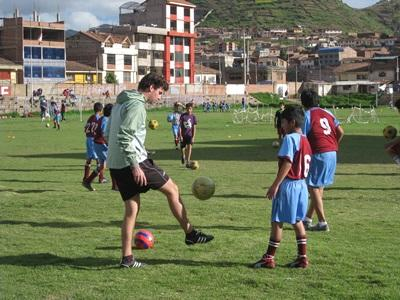 A child watches a Projects Abroad volunteer kick a ball at a soccer practice session in Peru
